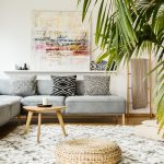 Pouf and wooden table in modern living room with painting above grey corner couch. Real photo