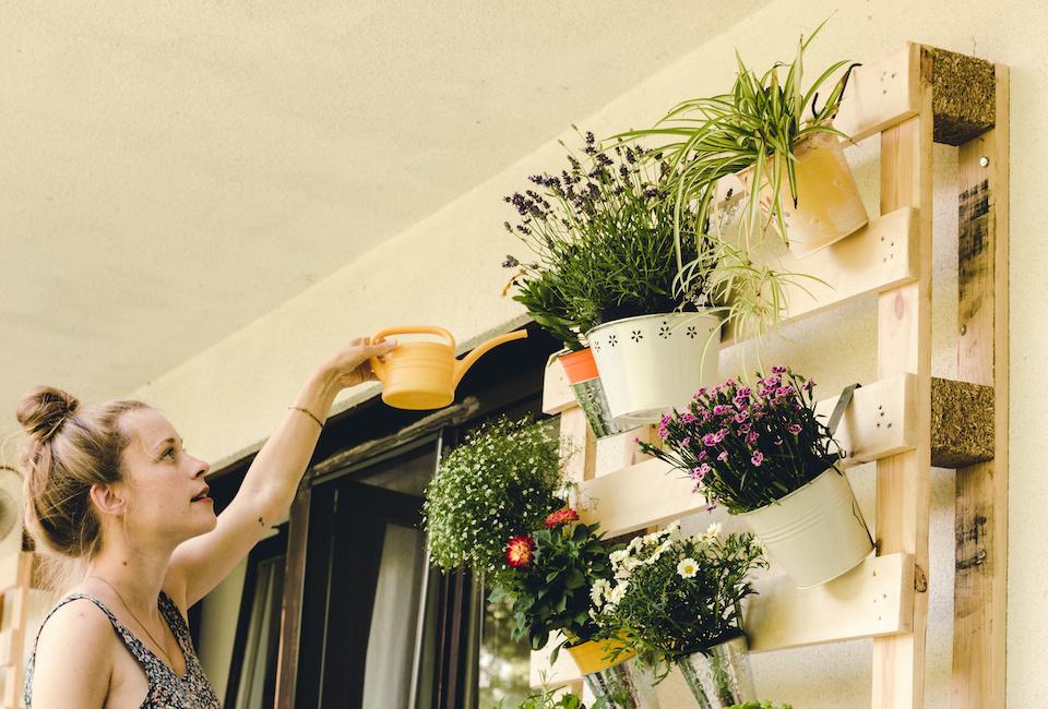 Donna innaffia piante su pensile realizzato con pallet