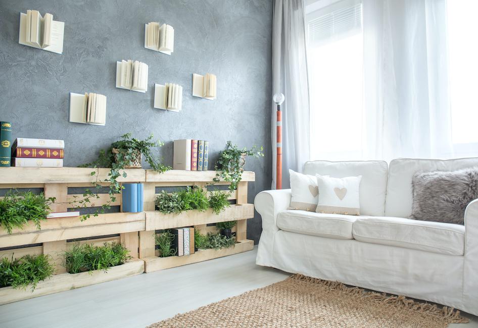 Salotto con sofà e libreria ricavata da un pallet