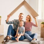 Una giovane famiglia felice tiene un tetto di cartone sopra la testa in una nuova casa subito dopo il trasloco, con attorno gli scatoloni