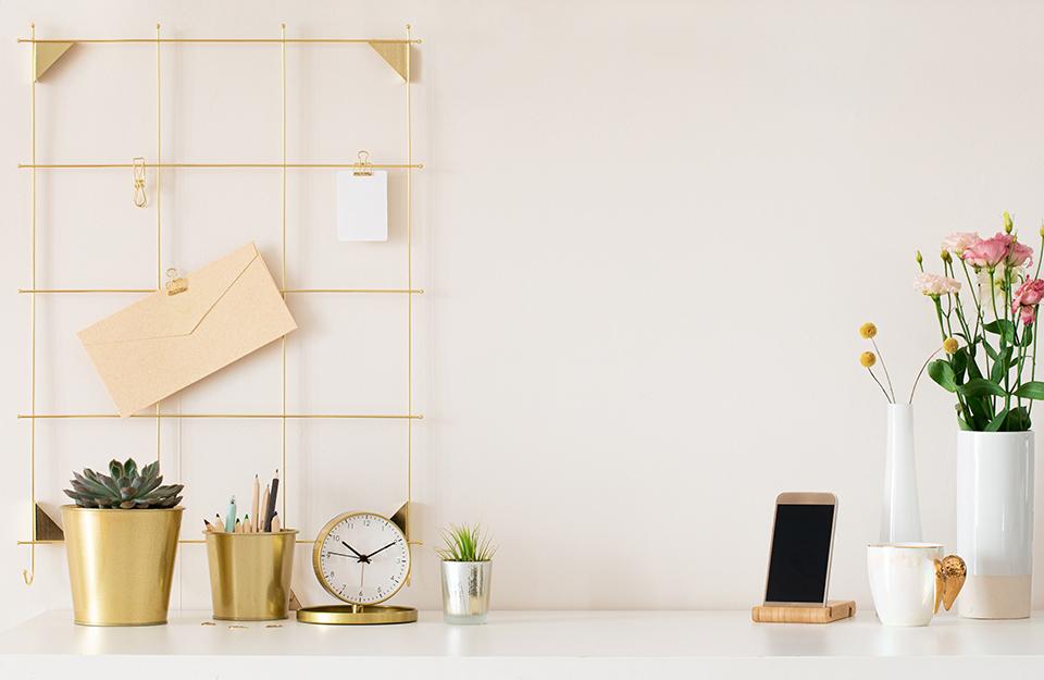 Scrivania con oggetti metallizzati (sveglia, portamatite e vaso) oltre a vasi e supporto per smartphone