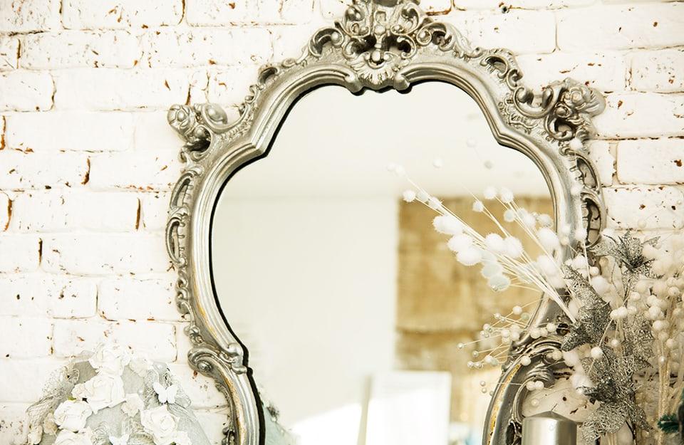 Un antico specchio dalla cornice elaborata a effetto metallizzato