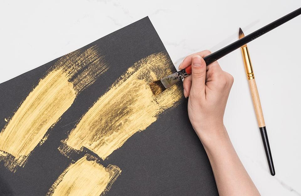 Mano che dipinge su foglio nero con vernice dorata