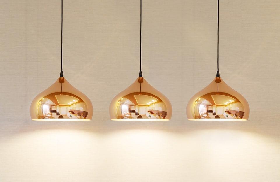 Tre lampadari metallizzati in stile minimal su fondo neutro
