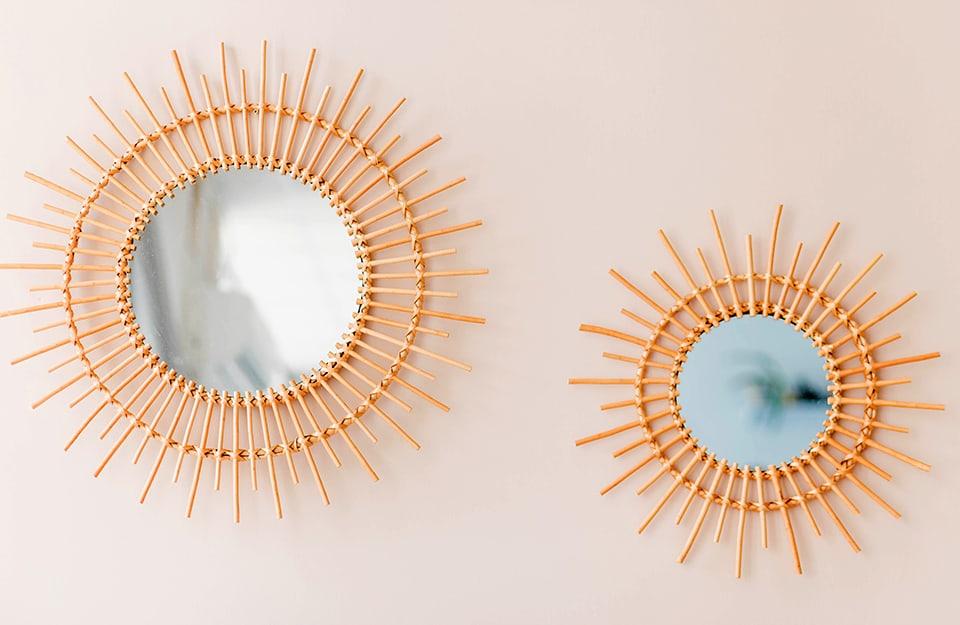 Una coppia di specchi rotondi di diverse dimensioni, entrambi con cornici a raggiera metallizzate