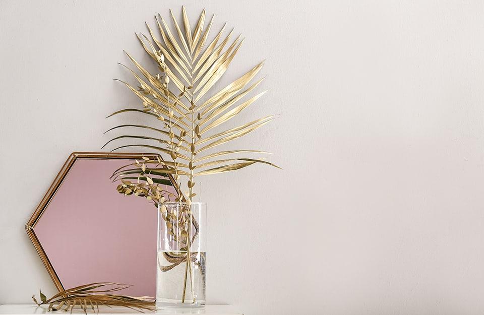 Delle foglie dipinte d'oro usate come decorazioni in una composizione di soprammobili