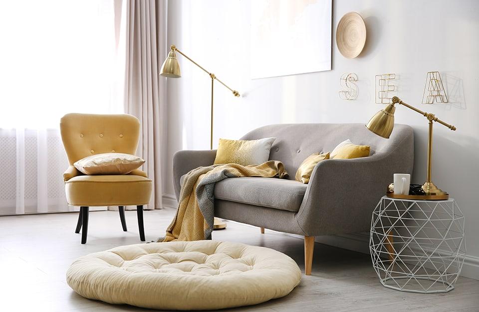 Salotto in stile scandinavo con dettagli dorati, comprese due lampade, una da terra e una da tavolo