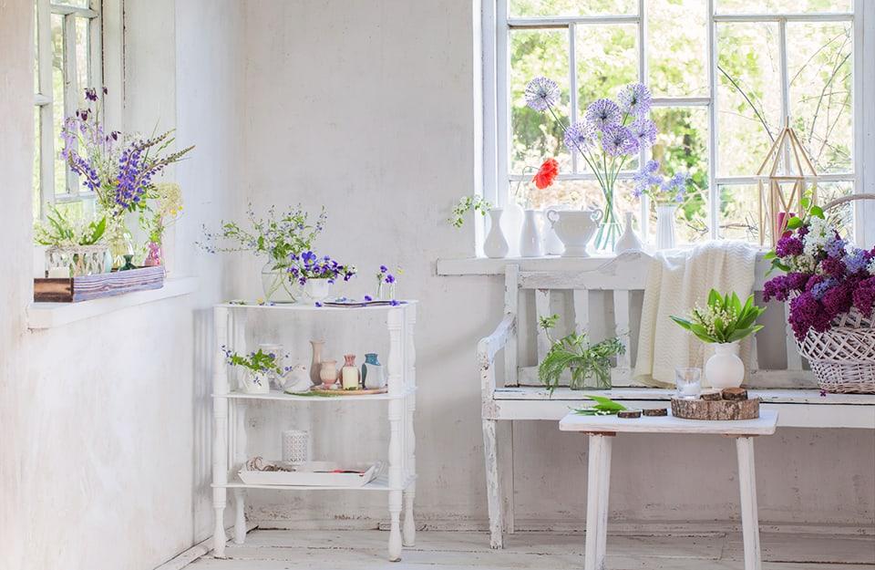Angolo domestico molto luminoso, in stile shabby chic, con arredi bianchi e molti fiori. Da una finestra si intravede un giadino