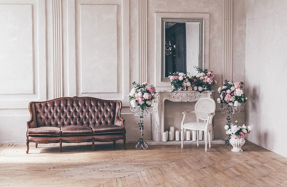 Angolo di un salotto in stile shabby chic romantico, con un sofa in pelle marrone a tre posti, camino sormontato da specchio, sedia antica bianca, decorazioni floreali, pareti bianche con cornici e parquet