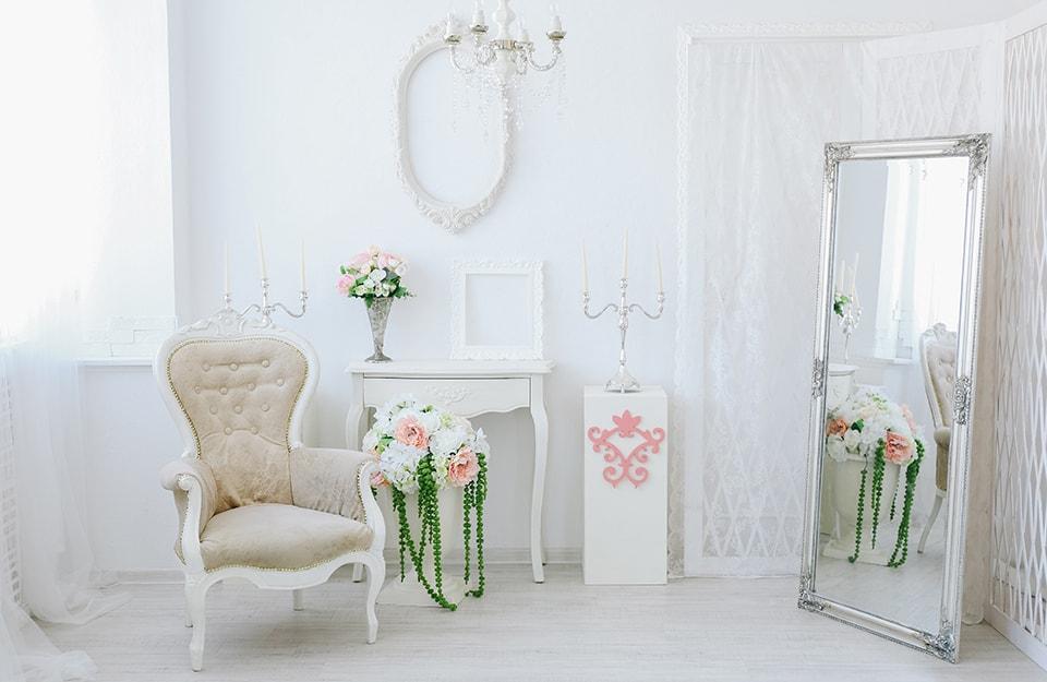 Angolo di un salotto bianco in stile shabby, con poltrona antica, lampadario a candelabro, grande specchio a terra, decorazioni floreali, consolle e cornici vuote decorative