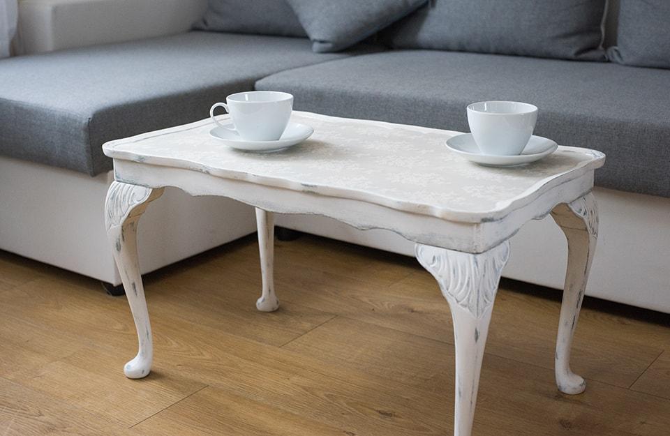 Tavolino da caffè bianco in stile shabby chic, con sopra due tazze. Sullo sfondo si vede parte di un sofà moderno