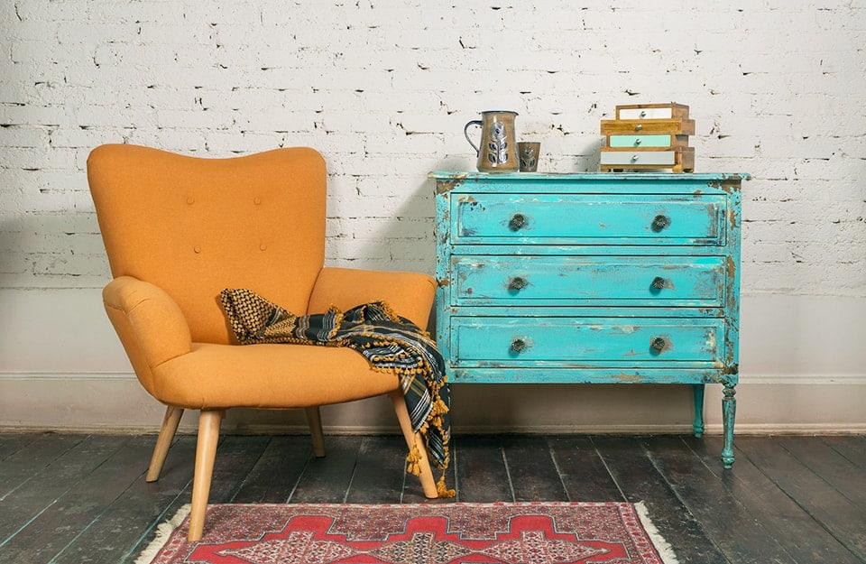 Angolo stile industrial shabby chic, con portona di modernariato arancione e cassettiera azzurra vintage