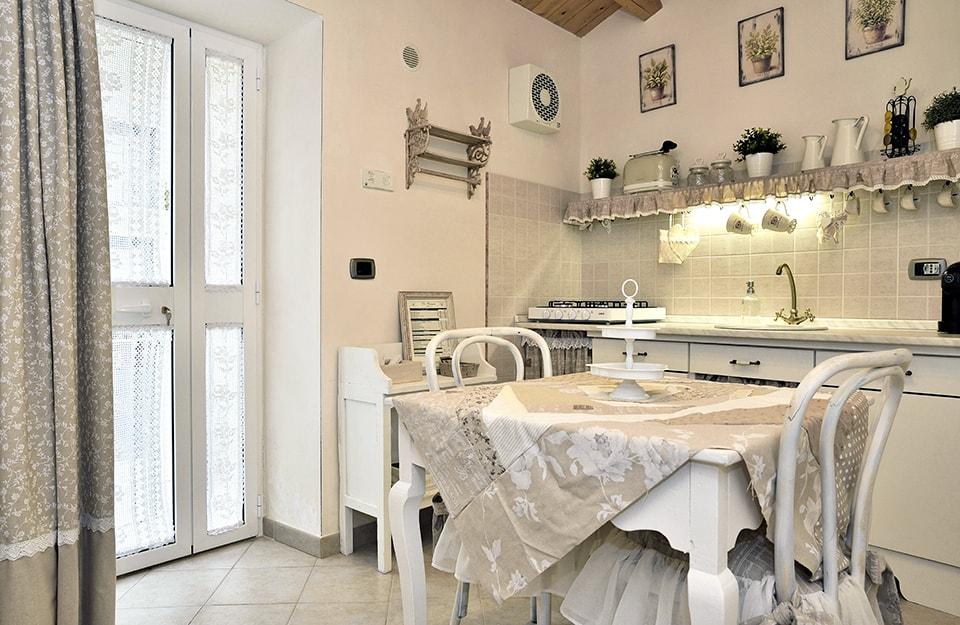 Cucina bianca con tavolo, sedie e scaffali in stile shabby chic