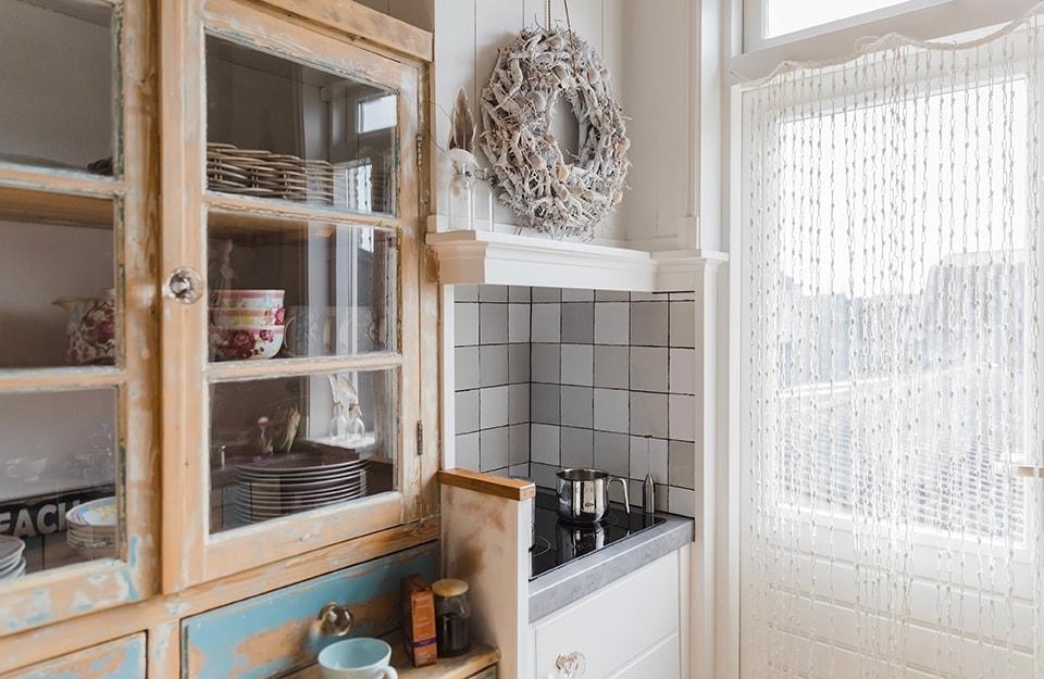 Angolo di una cucina in stile shabby chic. Si intravede una vecchia credenza con ante vetrate