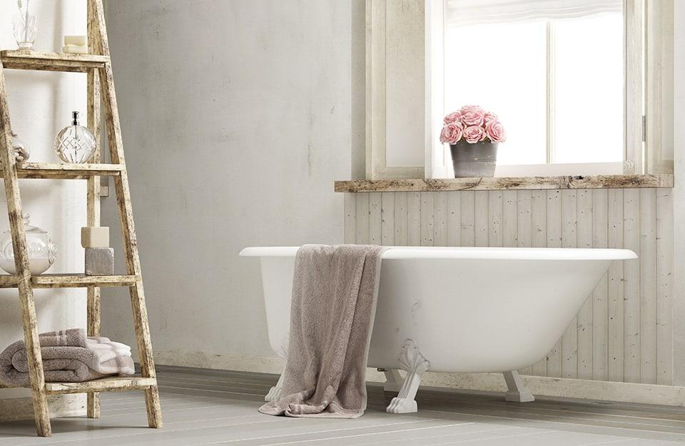 Sala da bagno in stile shabby chic. C'è una vasca da bagno antica sotto a una finestra. Sul davanzale un vaso di fiori. Una vecchia scala è appoggiata al muro e usata come portaoggetti