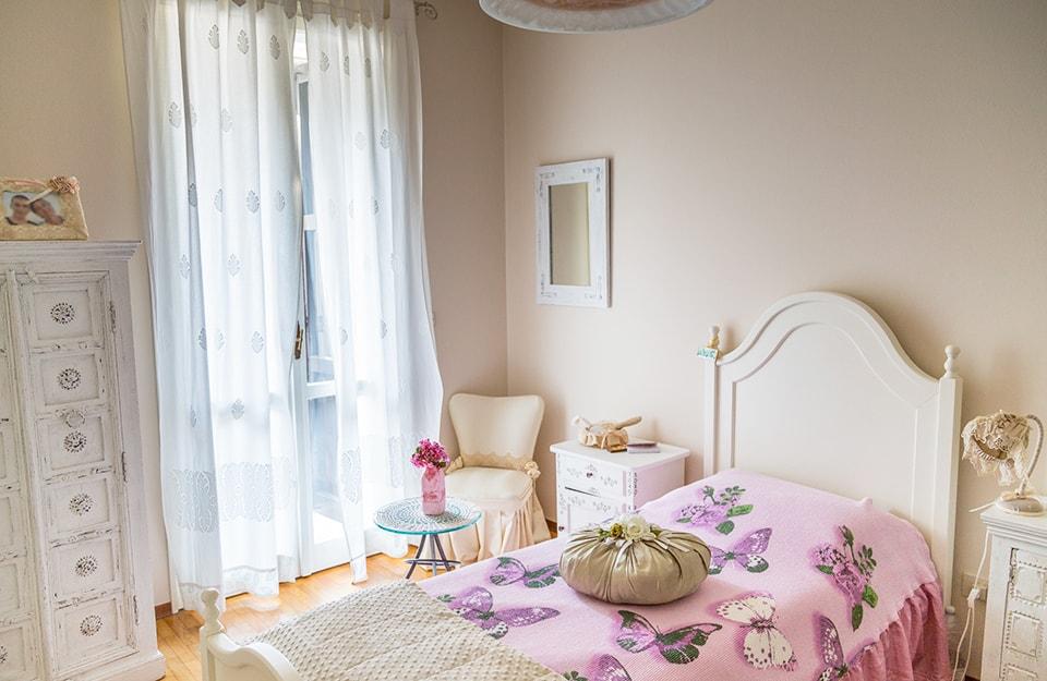 Camera da letto romantica con letto, comodino e poltrona in stile shabby chic