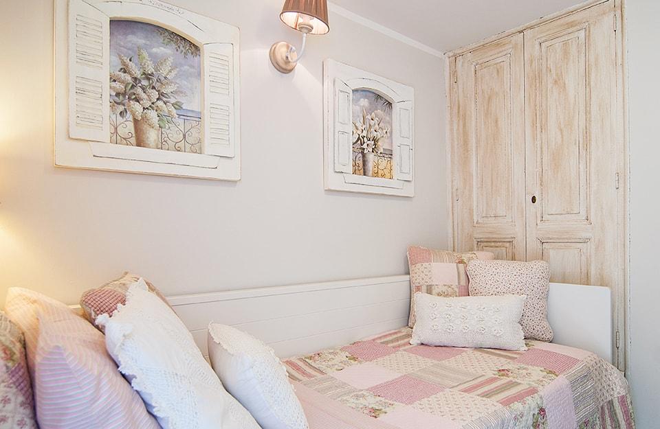 Camera da letto romantica con coperta patchwork rosa, quadri trompe-l'oeil che simulano delle finestre con vasi fioriti e un vecchio armadio restaurato in stille shabby chic