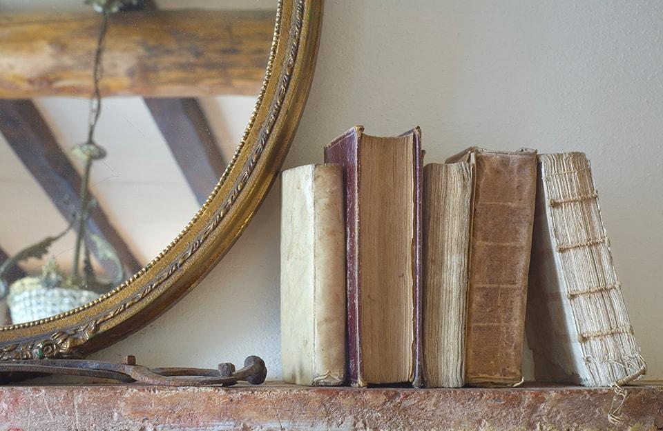 Degli antichi libri poggiati sulla mensola di un camino accanto a uno specchio dalla cornice vintage