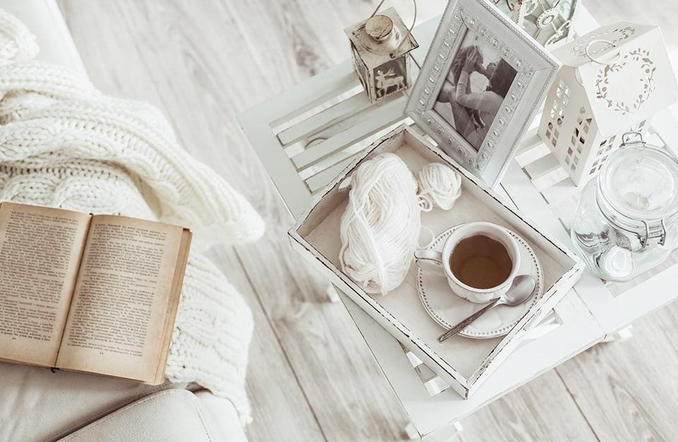 Primo piano su composizione stile shabby chic. Sopra un tavolino da caffè con pianale realizzato con una vecchia persiana c'è un vassoio da colazione con un tazza di tè e dei gomitoli di lana bianca. Sul tavolo ci sono pure una cornice e altri soprammobili, tutti sul bianco, così come bianca è la stanza. Un angolo di divano con una coperta e un vecchio libro aperto appare sulla sinistra