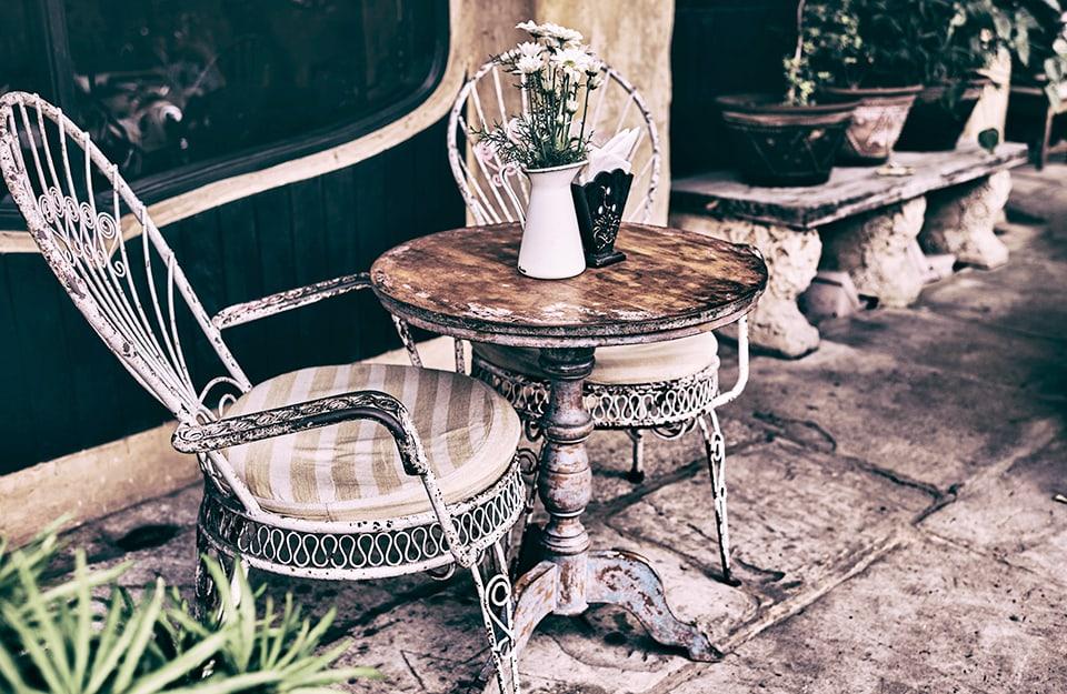 Ambiente esterno con tavolino e due sedie in stile shabby chic. Sul tavolo ci sono un vaso con fiori e un porta-tovaglioli