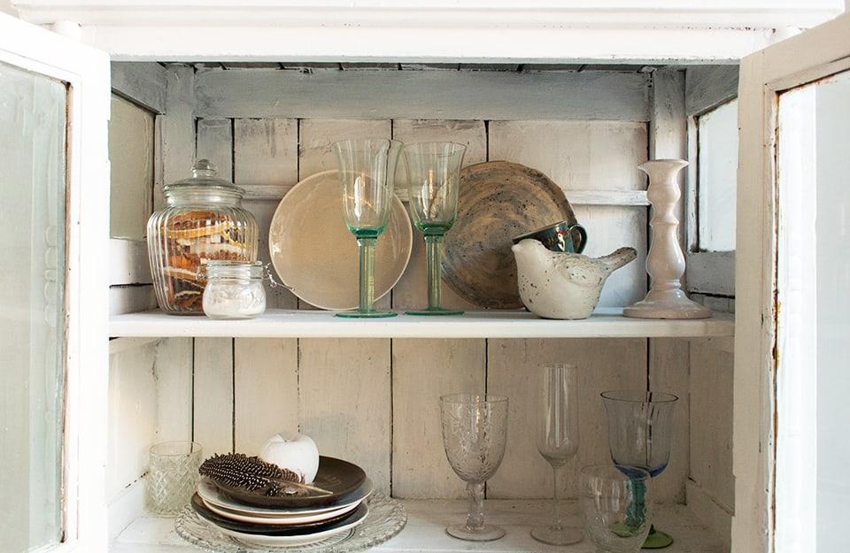 Dettaglio di una credenza bianca in stile shabby. Le ante sono aperte e si vedono oggetti per la tavola (piatti, bicchieri) e soprammobili